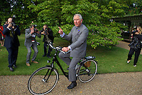 Prince Charles rides an electric bicycle during a sustainable environment fair in the Clarence House Gardens in St. James's Palace