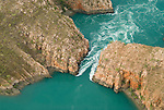Aerial of the horizontal waterfalls located deep within Talbot Bay in the Buccaneer Archipelago. Massive tidal movements create a waterfall effect as water banks up against one side of the narrow cliff passage, to be repeated again on the turning tide.  The twin gaps are part of the McLarty Ranges, which have two ridges running parallel approximately 300 metres apart. The first and most seaward gap is about 20 metres wide and the second, most spectacular, gap is about 10 metres wide..On a slack tide it is possible to drive boats through the two gaps to the bay behind. The tides in this area have a 10 metre variation which occurs over six and a half hours from low tide to high tide and vice versa. The effect of the waterfalls is created by the tide building up in front of the gaps faster than it can flow through them and there can be a four metre high waterfall between the bays..Derby, Western Australia