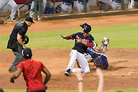 AZL Indians 1 right fielder Johnathan Rodriguez (30) looks to home plate umpire Glen Meyerhofer after sliding across home plate ahead of the tag from catcher David Garcia (9) during an Arizona League playoff game against the AZL Rangers at Goodyear Ballpark on August 28, 2018 in Goodyear, Arizona. The AZL Rangers defeated the AZL Indians 1 7-4. (Zachary Lucy/Four Seam Images)
