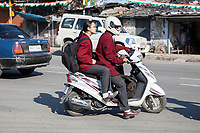 India, Dehradun.  Young Couple on a Motorbike--Helmet for the Man, none for the Woman.