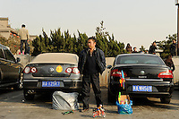 CHINA, Province Shaanxi, city Xian, VW Volkswagen and Skoad car, street vendor selling plastic toys