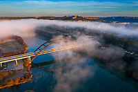 In this aerial image, clouds engulf the cliffs over Lake Austin, but leave an opening over the 360 Pennybacker Bridge where the cars zooming over the bridge fan the clouds away leaving a clear view of this iconic bridge.