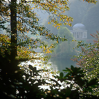 A hazy romantic view across the lake at Stourhead to an 18th century neo-classical temple