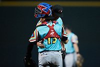 Llamas de Hickory pitcher Justin Slaten (27) hugs catcher David García (13) after getting the final out of the game against the Winston-Salem Rayados at Truist Stadium on July 6, 2021 in Winston-Salem, North Carolina. (Brian Westerholt/Four Seam Images)