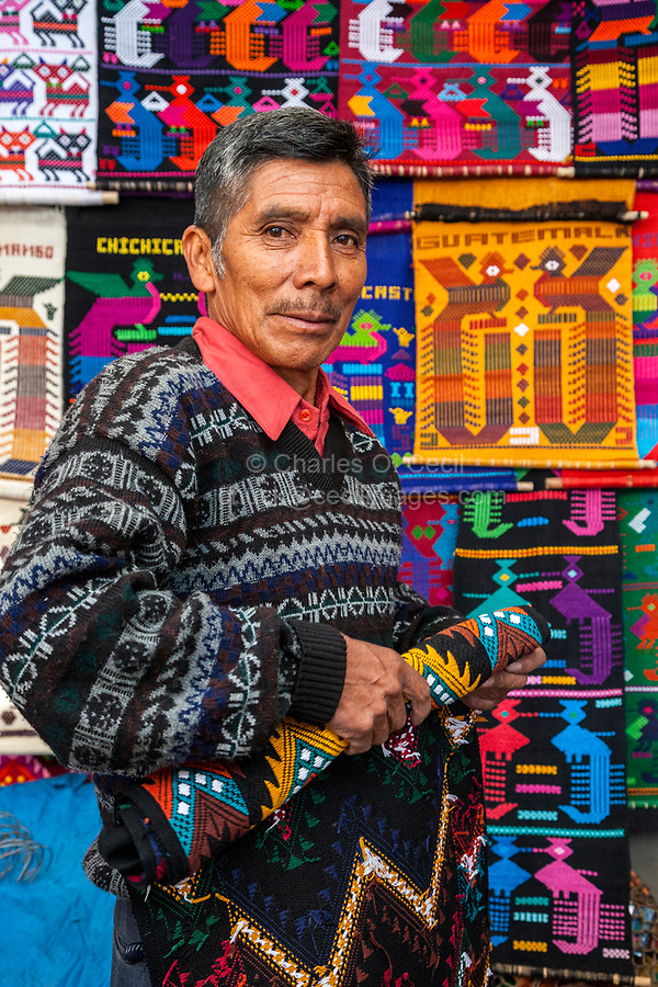 Chichicastenango, Guatemala.  Vendor of Wall Hangings and Souvenir Textiles in his Shop.