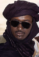Akadaney, Niger.  Fulani Man wearing Tuareg Indigo Tagelmust, Sunglasses.  This is an example of how one culture, the Fulani, in close contact with another, may adopt the other's clothing styles.