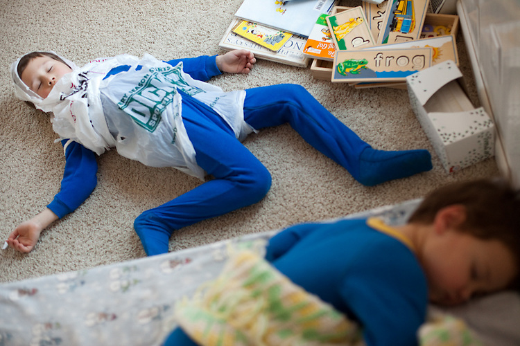 """On an especially cold winter day, both of my sons decided to put on their pajamas after lunch. They were delighted to wear the same color. My older son, age six, constructed an outfit out of shopping bags, and """"played dead"""" as I went to wake his brother up from a nap."""