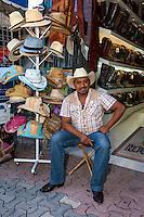 Store Clerk Selling Hats and Boots.  Playa del Carmen, Riviera Maya, Yucatan, Mexico.