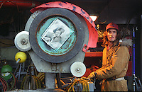 Aboard the deck of the F/V Big Valley, crewmen Eric Grumpke runs the hydrolics next to the crab coiler which bears a picture of Barbara Stanwyck, star of the television show that is the boat?s namesake, while the boat is in King Cove, Alaska preparing for the red king crab season on October 29, 1993. Grumpke drove the crane that shifted gear and equipment on deck.  In the winter, arctic nights last 18 hours. The sun barely comes above the horizon before it begins its retreat back below the surface.  Everyone's eyes adjust to the long winter nights, creating a glassy-eyed crew. The ?Aleutian stare? is a common affliction everyone gets as a result of fatigue and being in this empty, gray world for indefinite periods of time. Heart failure killed Grumpke only 19 days after this picture was taken while he was driving the boat...
