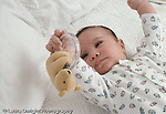 2 month old baby boy on back grasping toy horizontal