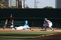 Sean Bouchard (5) of the UCLA Bruins takes a throw at first base while Zack Gahagan (10) of the North Carolina Tar Heels dives back to the bag during a game at Jackie Robinson Stadium on February 20, 2016 in Los Angeles, California. UCLA defeated North Carolina, 6-5. (Larry Goren/Four Seam Images)