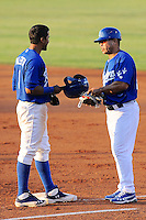 Ogden Raptors second baseman Jesmuel Valentin (6) and first base coach Leo Garcia (26) talk at first base against the Missoula Osprey at Lindquist Field on July 17, 2013 in Ogden Utah. (Stephen Smith/Four Seam Images)
