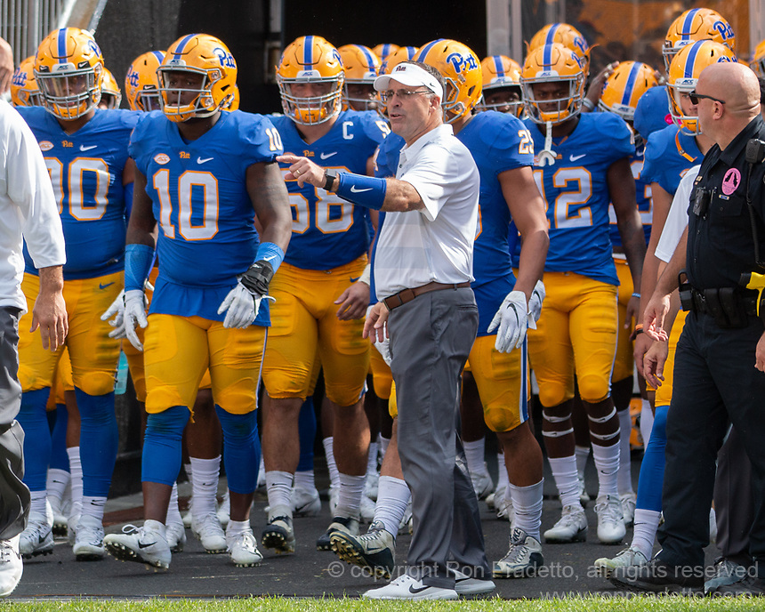 Pitt head coach Pat Naduzzi (white shirt) brings his team onto the field after a rain delay. The Pitt Panthers defeated the Syracuse Orange 44-37 in overtime at Heinz Field in Pittsburgh, Pennsylvania on October 6, 2018.