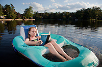 Preteen girl reading a book while floating in an inner tube on a public lake