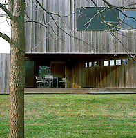 facade of the house...In a four acre plot of land in the Hamptons in New York is located the house of Nikos Zografos. In his minimal two-storey wooden penthouse, metal, granite, marble and leather are the main elements of his decoration style.