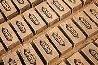Rajasthan, India.  Freshly-molded Bricks Drying in the Sun prior to going to Underground Ovens for Firing.  Note Hindu swastika in Company Logo.