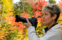 Tourist taking photographs of Fall foliage, Kancamagus Highway, near Conway, New Hampshire