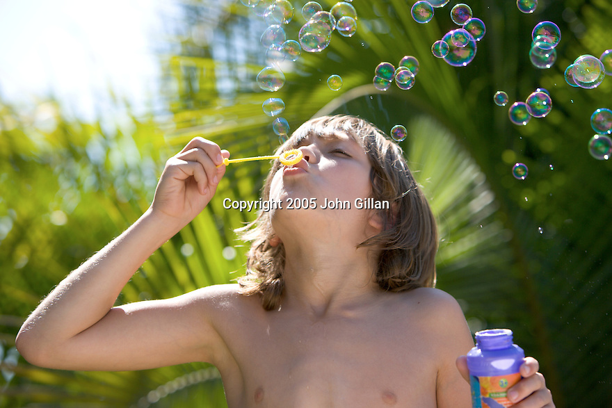 Child blowing bubbles outside in the sunshine with palm tree in the background. File # WX3P0751