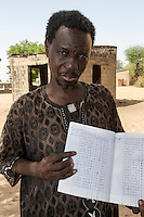 Storeroom Steward Shows Inventory Book at Bijam, a Wolof Village, near Kaolack, Senegal. DOZENS MORE OF IMAGES RELATED TO MILLET CULTIVATION ARE AVAILABLE.  WHAT DO YOU NEED?