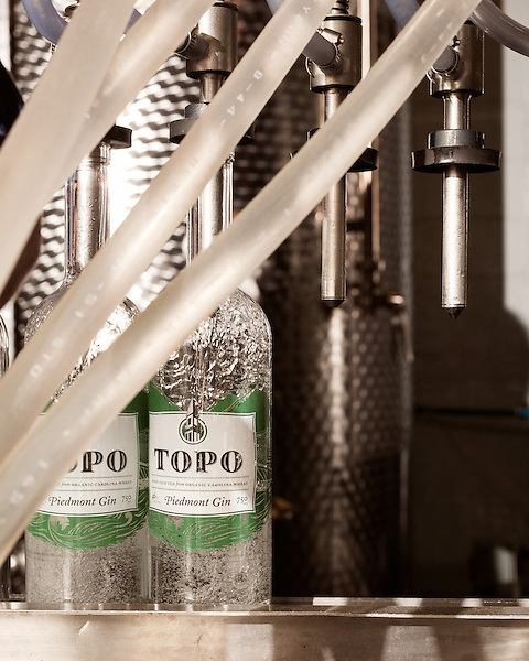 June 18, 2013. Chapel Hill, North Carolina<br />  Head distiller George Dusek fills bottles of TOPO Gin with a repurposed milking machine.<br />  TOPO, Top of the Hill Distillery, the brainchild of owner Scott Maitland and Spirit Guide Esteban McMahan, is located in the old N&O Building on Franklin Street. Making gin, vodka and American whiskey from locally sourced wheat, they are one of the few distilleries bringing  organic liquor to ABC shelves around the state.