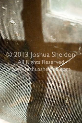 Shadow of cross on window screen<br />