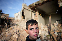 SYRIA, 02.2012, village of Kureen, Idlib province. © Timo Vogt/EST&OST. A boy in front of a totally destroyed house after an assault by Syrian government troops. On February 22 the Syrian army attacked the village. Kureen was among the first villages in the northwest of Syria controlled by the opposition. Some villagers and members of the defence units escaped to surrounding olive orchards when the attack began in the early morning. A majority of the inhabitants didn´t manage to escape. The heavy shelling lasted 7 hours. Soldiers searched all houses, burnt some of them down, looted shops, stole cars and furniture. About 60 motorcycles were destroyed. Tanks demolished several houses. 6 men were executed. One woman died as a result of an heart attack.