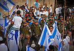 Israeli border police officers walk past youth dancing and waving flags outside Damascus gate in Jerusalem Wednesday May 28 2014, during festivities marking Jerusalem day. The Day marks the reunification of Jerusalem following the 1967 Six Day War when Israel captured the Arab part of the city from Jordan. Photo By Eyal Warshavsky