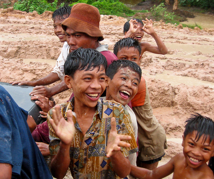 A group of local Cambodian men and children try to push a stuck car out of the mud