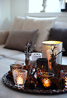 A dish of festive cheer - pine cones, glittering glasses lit with tea lights and soft reindeer sparkle on the living room coffee table