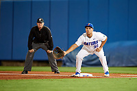 Florida Gators first baseman Keenan Bell (32) holds a runner on as umpire Chris Tipton looks on during a game against the Siena Saints on February 16, 2018 at Alfred A. McKethan Stadium in Gainesville, Florida.  Florida defeated Siena 7-1.  (Mike Janes/Four Seam Images)