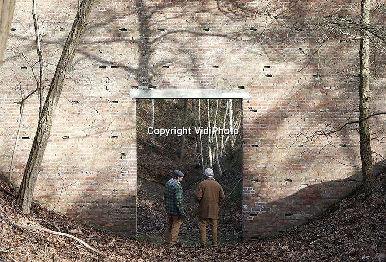 Foto: VidiPhoto<br /> <br /> SOESTERBERG – Een afgelegen herdenkingsplek, diep in de bossen van de voormalige vliegbasis Soesterberg, herinnert aan de executie van 33 Nederlandse verzetsstrijders op 19 november 1942 door de Duitze bezetter. Het enige dat ze met plek gemeen hebben, is dat ze naar deze toen Duitse vliegbasis werden getransporteerd en daar achter de schietbaan door een vuurpeloton in koelen bloede werden vermoord. Om de schoten te camoufleren vonden er op dat moment aan de voorzijde schietoefeningen plaats door Duitse soldaten. Vrijwilligers van het Nationaal Militair Museum Herman van den Berg en Adriaan van Hemert (met pet), hebben zich in deze vrij onbekend gebleven massa-executie verdiept. Foto: De stenen muur vlak bij de fussilladeplek.