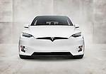 White 2017 Tesla Model X luxury SUV electric car front view on concrete wall background Image © MaximImages, License at https://www.maximimages.com