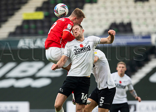 7th November 2020; Pride Park, Derby, East Midlands; English Football League Championship Football, Derby County versus Barnsley; Cauley Woodrow of Barnsley leaps above Matthew Clarke of Derby County to head the ball in the Derby goal area