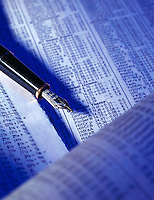 Fountain pen in blue lighting, resting atop the financial section of a newspaper.