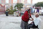 Romania, Tirgu Jiu - A woman is shaving her blind brother at their house's yard in Meteor district, an area inhabited by ROMa people.