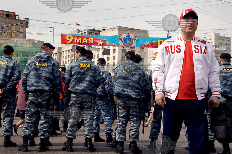 """A man in """"Russia"""" jacket stands in front of riot police guarding a demonstration by Communist supporters on Labour Day. © Justin Jin"""