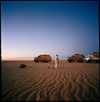 Sahara desert, Libya-Chad, November/December 2004..Every week, a convoy of 40 privately owned Libyan trucks loaded by the WFP with about 1000 metric tons of western food aid cross 2500 km of deep desert across Libya and Chad to reach more than 200 000 refugees from Darfur in camps near the Sudanese border. Moussa's evening prayer.