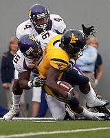 East Carolina defensive end C.J. Wilson (95) and safety Van Eskridge (4) tackle WVU running back Noel Devine. The WVU Mountaineers defeated the East Carolina Pirates 35-20 at Mountaineer Field at Milan Puskar Stadium, Morgantown, West Virginia on September 12, 2009.