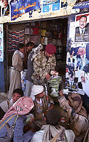 Posters of the Yemeni President Ali Abdullah Saleh look down on a member of the Yemeni army buying qat from armed tribesmen near Marib. Many Yemeni men sit and consume this narcotic plant for several hours a day, chewing the leaves to a pulp stored in the cheek like a golf ball.