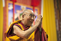 """Switzerland. Basel. St. Jakobshalle. His Holiness the Dalai Lama is greeting the audience at the end of his public lecture on Bodhicitta. He holds his hands kept close to the chest in devotional attitude with the palms and fingers joined as a sign of respect. The gesture is also called the simple namaste (prayer) position (means """"I bow to you.""""). The 14th and current Dalai Lama is Tenzin Gyatso, recognized since 1950. He is the current Dalai Lama, as well as the longest-lived incumbent, well known for his lifelong advocacy for Tibetans inside and outside Tibet. Dalai Lamas are amongst the head monks of the Gelug school, the newest of the schools of Tibetan Buddhism. The Dalai Lama, also called """" Ocean of Wisdom"""" is considered as the incarnation of Chenresi, the Bodhisattva of compassion who is also the protective deity of Tibet. 7.02.2015 © 2015 Didier Ruef"""