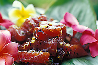 "Closeup of """"poke"""", a local favorite made with raw tuna, on a banana leaf with plumeria blossoms."