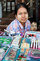 Myanmar, Burma.  Burmese Woman and Son Wearing Thanaka Paste on their Faces as a Cosmetic Sunscreen.  Bagan Market.