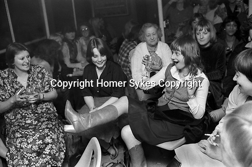 Girls only night out. Hen party on river Thames boat London 1979. One older woman amongst a group of young women.