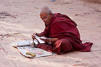 Bodhnath, Nepal.   A Monk Reading Holy Texts at the Buddhist Stupa of Bodhnath.
