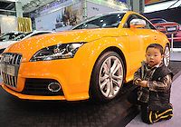 A boy sits near a AudiTTS car at the Hangzhou International Luxury Exhibition in Hangzhou, China 24 Jan 2010.<br /> <br /> PHOTOS BY SINOPIX