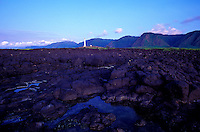 Rocky shoreline near the point on the Kalaupapa peninsula, with the lighthouse in the background