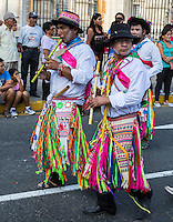 Lima, Peru.  Two Peruvian Men with Flutes Marching in an Andean Cultural Parade, Plaza de Armas.