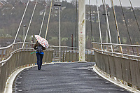 Pictured: A woman tries to shield herself from the strong wind as she walks on the footbridge over river Towy in Carmarthen, Wales, UK. Wednesday 10 March 2021<br /> Re: Strong gales are expected in places in areas of Wales.<br /> Coastal and hilly areas could see gusts of up to 70mph.<br /> There a warning in place from 9pm on Wednesday to 3pm on Thursday, with heavy showers also forecast.