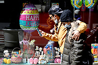 NEW YORK - NEW YORK - APRIL 03: People walk in front of Easter decorations displaying in a store window on April 03, 2021 in New York. NYC and most of the United States are planning a year later after pandemic, the celebration of the of Easter which may return with some of normalcy under New York state guidelines. (Photo by John Smith/VIEWpress)