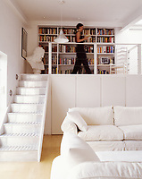 Victoria O'Brien walks across the library gallery space in her open plan loft living room